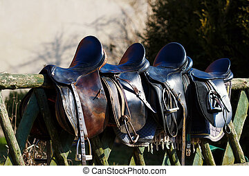 Leather saddle horse - A saddles laying on the rustic fence ...