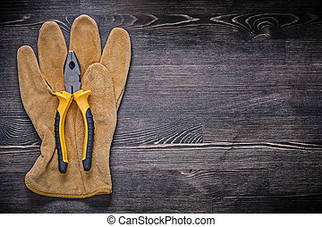 Leather safety glove tin snips on wooden board copy space.
