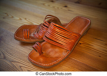 leather sandals on a wooden floor
