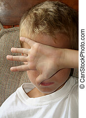 Leave Me Alone - Closeup of a 9 year old boy blocking his...