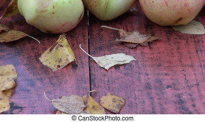 Leaves and apples on table in fall
