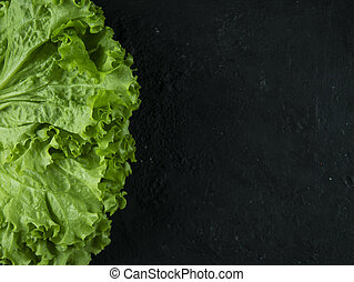 Leaves of fresh lettuce on a stone background.
