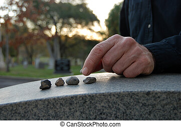 Leaving pebbles on headstone - Close up of a left hand...