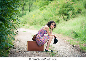 Leaving to an unknown destination: beautiful young woman ...