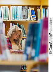 lectura del estudiante, libro, entre, estantería, en, el, biblioteca