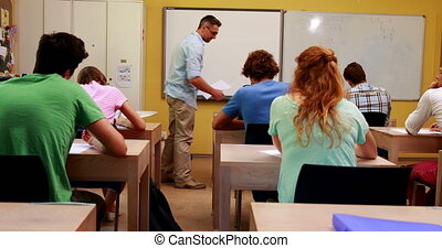 Lecturer handing out assignments to his students in classroom at the university