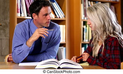 Lecturer helping his confused student in the library at the...