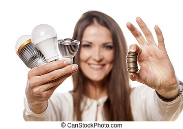 LED concept - smiling girl holding the LED bulbs in one hand...