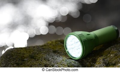 LED flashlight at waterside - LED flashlight on the mossy...