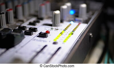 LED Indicator Level Signal on the Sound Mixing Console. Fade sliders controls in music studio, close-up. Led light output level indicator. Volume level changes with green, yellow and red indicator lights
