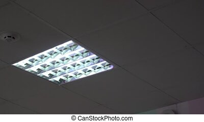 led lamp on the white ceiling near smoke detector.