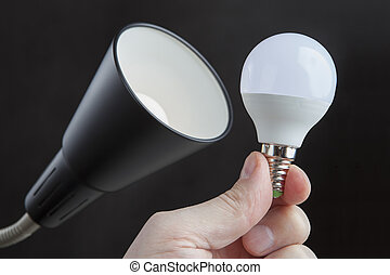 LED light bulb in human hand close to the luminaire.