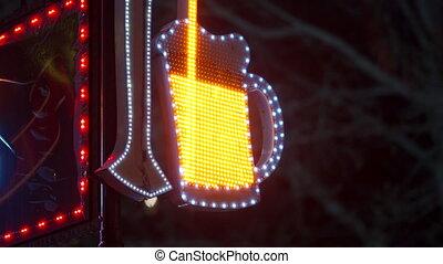 LED restaurant light sign decoration at dusk, illuminated pub bar neon sign beer tankard on night city street.
