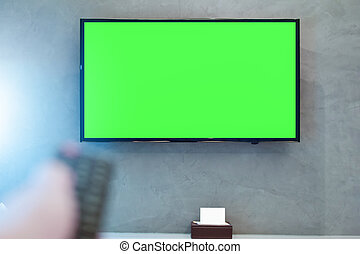LED screen TV with green screen compositing. TV or television - green screen on the wall in modern room with blurred hand on remote