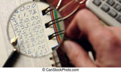 Ledger papers are watched with magnifier. Financial...