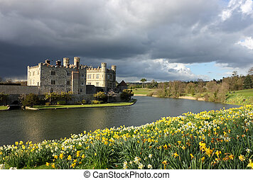 Leeds Castle in Kent, United Kingdom with blooming daffodils and dramatic sky.
