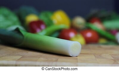 Leek on a chopping board and vegetables