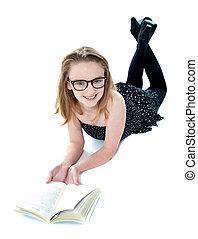 leende liten flicka, lögnaktig, med, en öppen bok