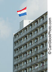 Dutch flag on top of a block of flats against the blue sky