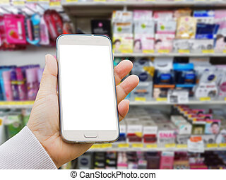 left asian hand with pullover holding smart phone on blurred background of various brand of skincare and cosmetic products in packaging for sale on supermarket stand or shelf.
