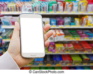 left asian hand with pullover holding blank screen smart phone on blurred background of various brand of lozenge and gum in packaging for sale on supermarket stand or shelf