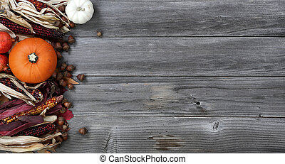 Left border of seasonal Autumn decorations on aged wood for the holiday background setting