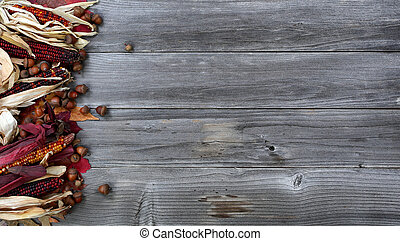 Left border of seasonal Autumn decorations on aged wood for the Thanksgiving holiday background setting