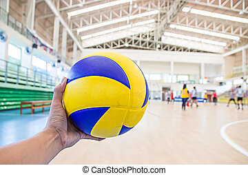left hand holds a volleyball
