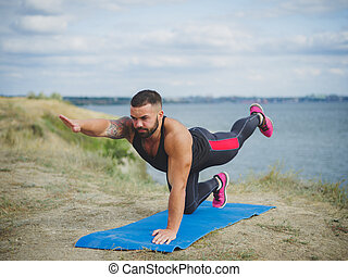 Left side of strong man practices yoga outside, near the river, on green mountain. Male training, hardowking person