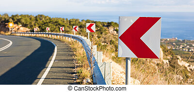 Left Turn Sign: Road signs warn of a sharp turn on a narrow road