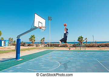 lefty slam dunk by the sea - basketball player slam dunk in...