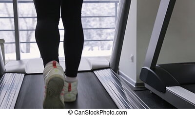 leg athlete woman walking on a treadmill in front of panoramic windows with views of the snowy forest