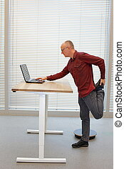leg exercise during standing office work -  middle age balding man in eyeglasses man  with laptop at the mobile table
