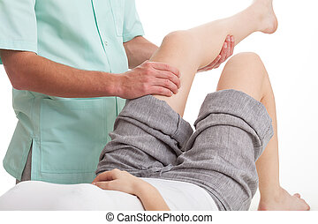 Physiotherapist dressed in green uniform massaging woman's leg