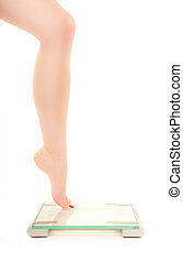 Slender leg of a woman fearing weight scale