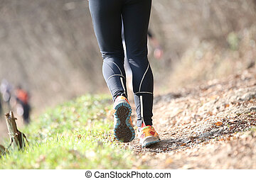 Leg of athlete runner from behind during racing on the mountain
