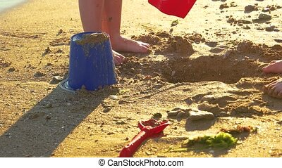 Leg of child stomping mud. - Kid pouring water from bucket....