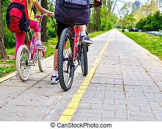 Leg of girls ride on bicycle.