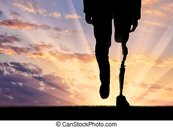 Leg with prosthesis on background sunset. Concept disabled person