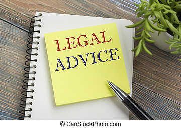 Legal Advice. Notepad with message, pen and flower. Office supplies on desk table top view