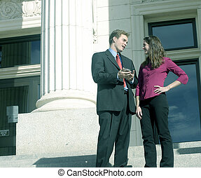 Successful man and woman are talking on the court steps with their pda