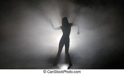 Leggy girl dancing in a smoky studio rhythmic dance. Silhouette