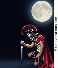 Legionary soldier standing on a knee at night time
