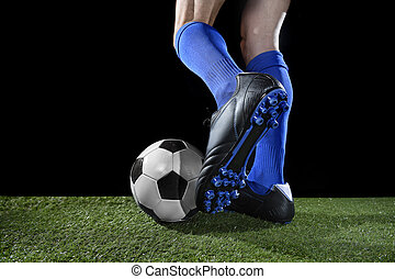 legs and feet of football player in action running and dribbling with the ball playing on green grass
