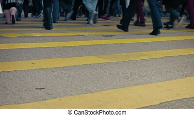 Low angle shot reveals the legs and feet of many pedestrians, crossing a busy and well lit, urban street at night. Video UltraHD