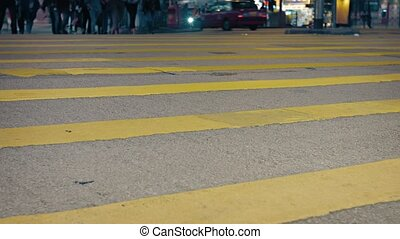 """Low angle shot reveals the legs and feet of many pedestrians, crossing a busy and well lit, urban street at night. Video Full HD"""