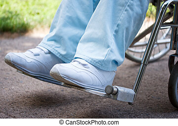Legs and feet of woman sitting in wheelchair outside
