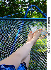Legs and hammock in tropical surroundings
