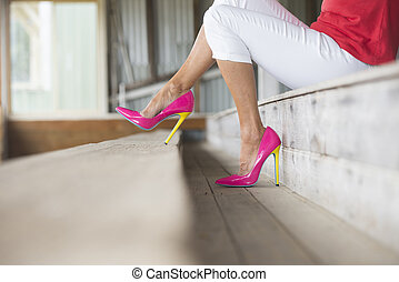 Legs and pink high heels sitting relaxed - Concept close up...