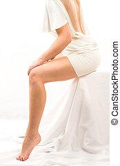 legs - beautiful woman sitting on something white. Isolated...
